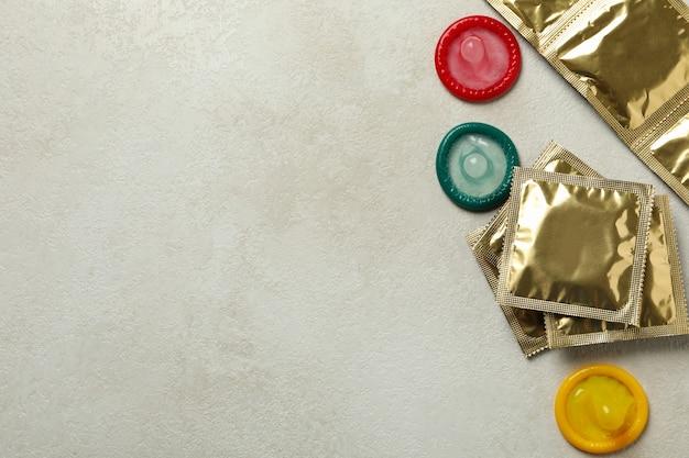 Condones multicolores sobre superficie con textura blanca
