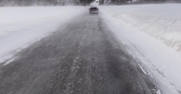 Conducción de automóviles en ventisca de invierno en carretera nevada en noruega
