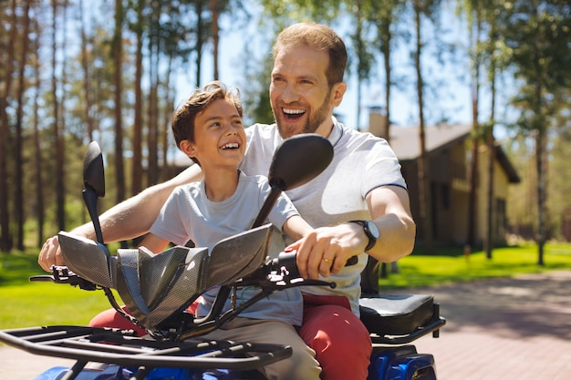 Conducción de velocidad. padre joven inspirado sonriendo y conduciendo un vehículo todo terreno con su hijo