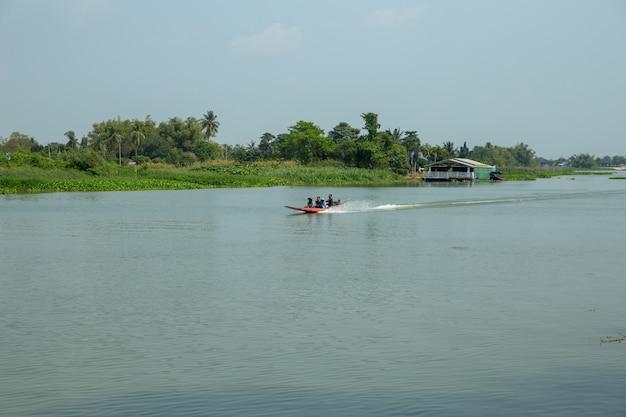 Conduce un bote a motor, controla hábilmente un bote a motor en el río, por la noche.