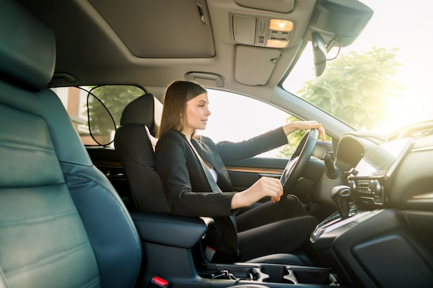 Conduciendo por la ciudad. mujer de negocios atractiva joven en traje negro sonriendo y mirando directamente mientras conduce un automóvil
