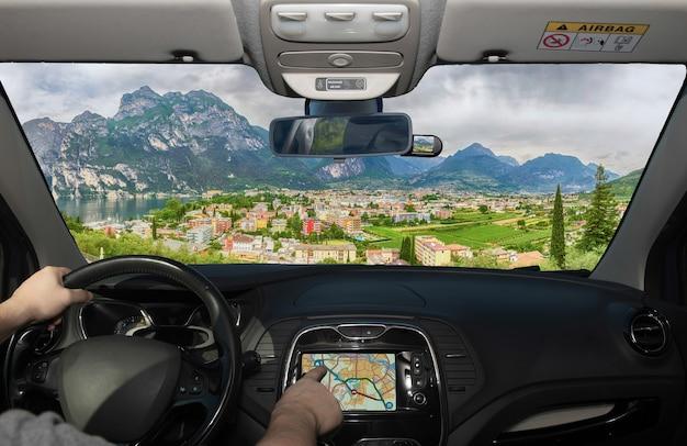Conducir un automóvil mientras usa la pantalla táctil de un sistema de navegación gps hacia riva del garda, en el norte del lago de garda, trento, italia