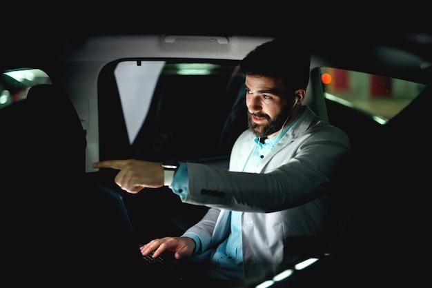 Conducir a casa trabajando hasta tarde, mostrando al asistente dónde girar. el empresario va a casa a trabajar tarde en la noche.