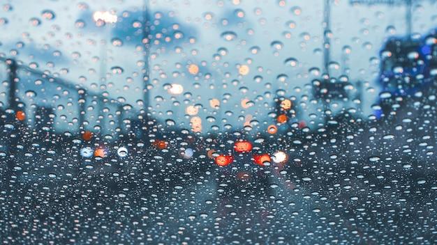 Conducir el coche en la carretera de la metrópoli en un atasco de tráfico con gotas de lluvia sobre el parabrisas