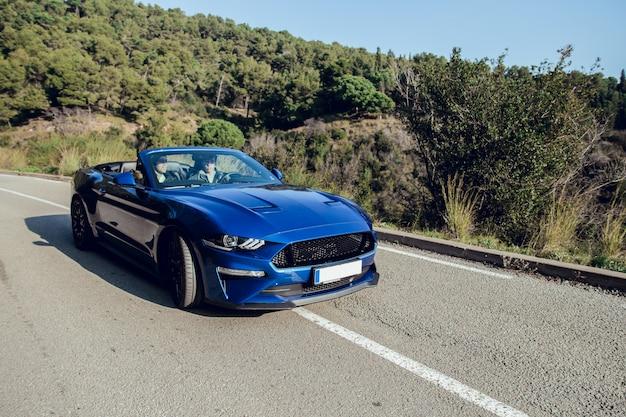 Conducir un coche deportivo descapotable por carretera.