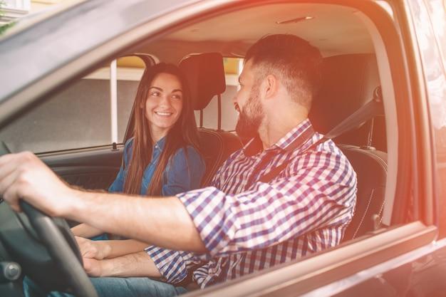 Conducir con cuidado. hermosa joven pareja sentada en los asientos del pasajero delantero y sonriendo mientras guapo hombre conduciendo un coche.