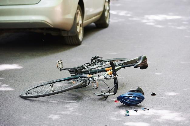 Conducir ebrio. bicicleta y accidente de coche de color plateado en la carretera en el bosque durante el día