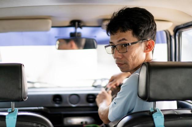 Conductor asiático conduciendo un coche antiguo y mirando hacia atrás desde el espejo