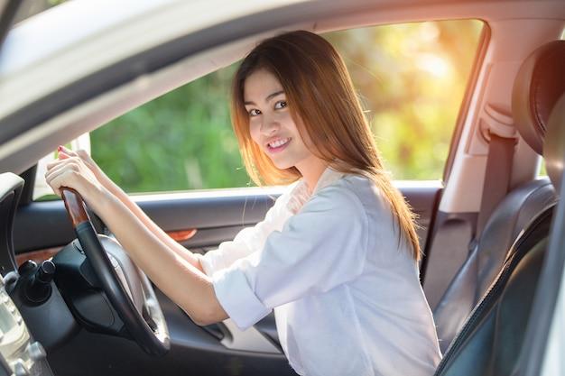Conductor asiático joven de la mujer que conduce un coche en el camino en campo.