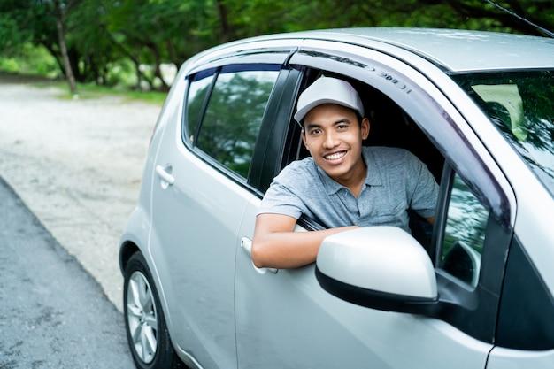 Conductor asiático mira desde la ventana abierta con una sonrisa