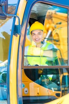 Conductor asiático sentado en la cabina de la maquinaria de construcción del sitio de construcción