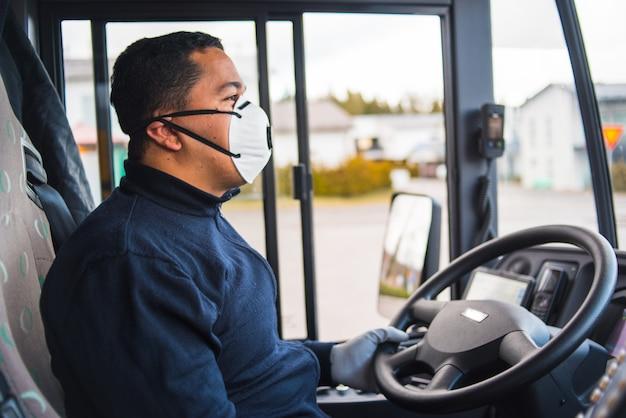 Conductor de autobús con máscara de protección y guantes que conducen autobuses interurbanos