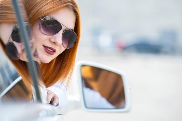 Conductor bonito joven de la mujer en gafas de sol que mira por la ventana delantera del coche en un día soleado de verano.