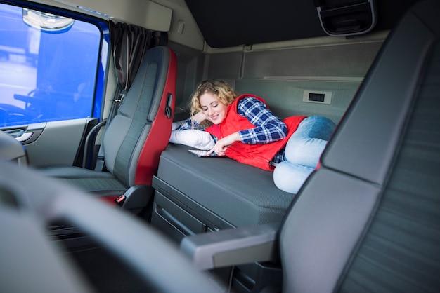 Conductor de camión acostado en la cama en su cabina comunicándose con su familia a través de una tableta