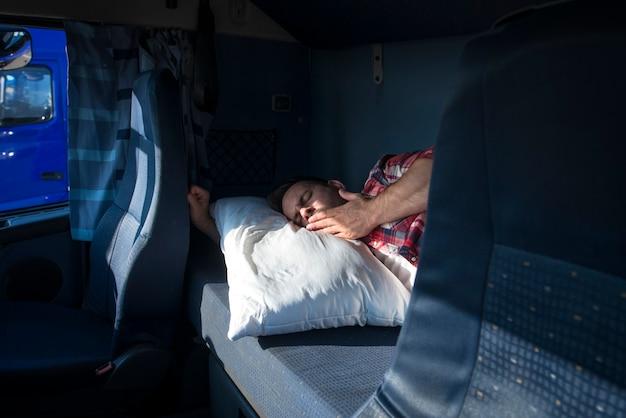 Conductor de camión bostezando y despertando en su cabina en la parada de camiones