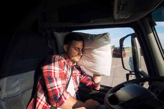 Conductor de camión durmiendo en la cabina de su camión debido a la conducción de largas distancias y al exceso de trabajo