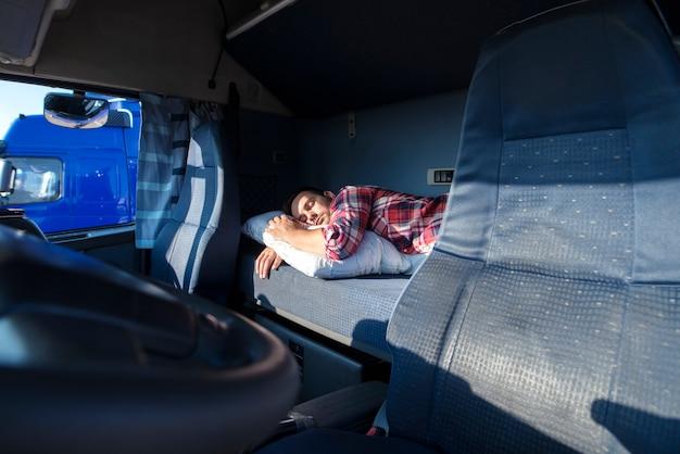 Conductor de camión durmiendo en la cama dentro del interior de la cabina del camión