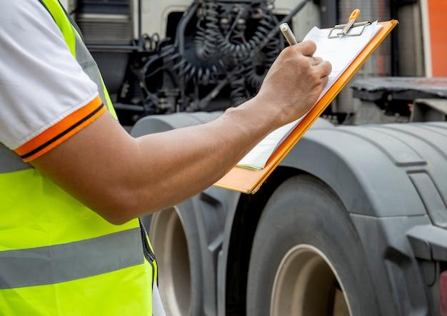 Conductor del camión está escribiendo en el portapapeles con la inspección de los camiones.