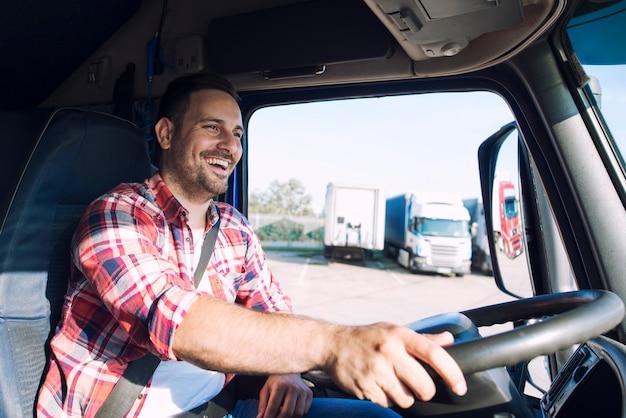 Conductor de camión profesional de mediana edad con ropa casual que conduce un vehículo de camión y entrega de carga a destino