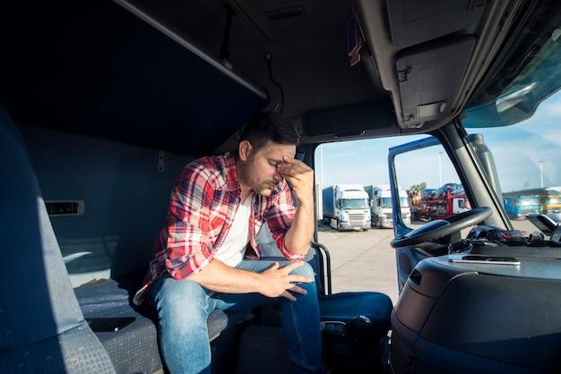 Conductor de camión sentado en la cabina de su camión sintiéndose preocupado y molesto
