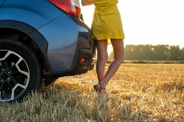 Conductor de chica joven con piernas delgadas en vestido de verano amarillo corto de pie cerca de su coche en el campo de paja seca