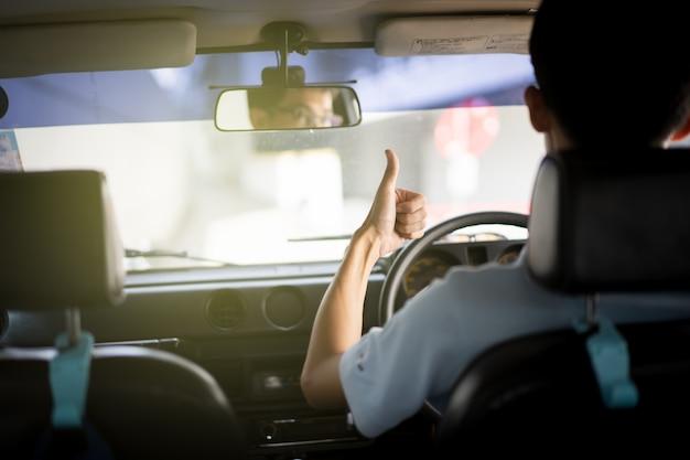 Conductor de coche asiático mostrando un pulgar hacia arriba. concepto de conducción segura