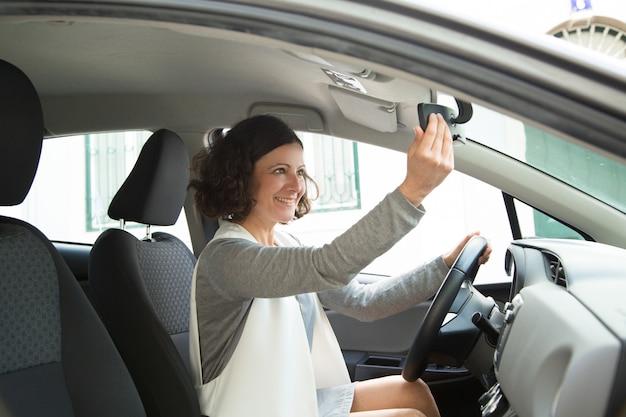Conductor de coche femenino alegre que mira en espejo