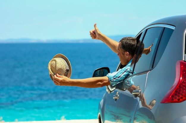 Un conductor en coche en el mar en verano.