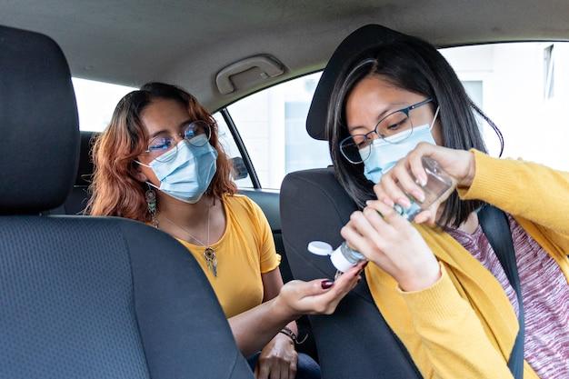 Conductor de coche pone gel antibacteriano en el pasajero del asiento trasero