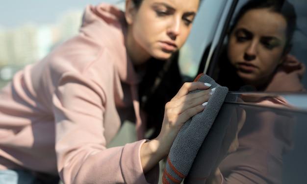 Conductor cuidando su auto y limpiándolo