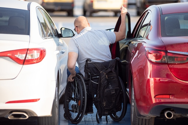 Conductor discapacitado joven en silla de ruedas fom coche rojo