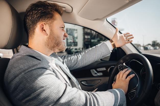 Conductor enojado en un atasco que pierde su manipulación y gesticula para dejar ir su auto. llegar tarde