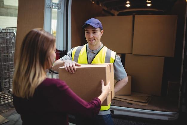 Conductor de entrega que entrega el paquete al cliente fuera de la furgoneta en el almacén