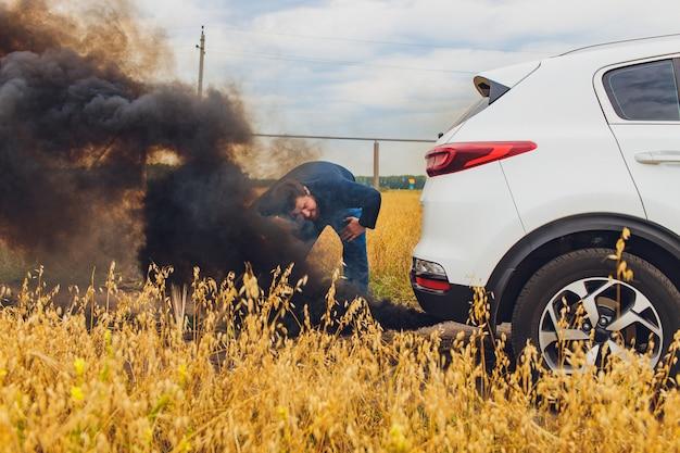 Conductor estresado y frustrado tirando de su cabello mientras está parado en la carretera junto al auto roto. problemas de viaje por carretera y conceptos de asistencia. fumar.