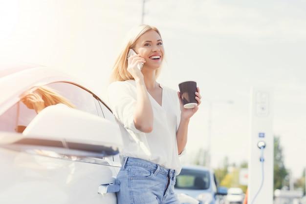 Conductor femenino feliz joven que habla en el teléfono