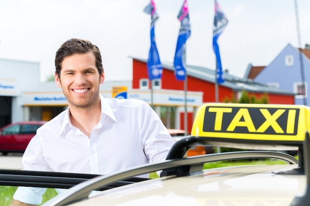 Conductor frente a taxi esperando clientes