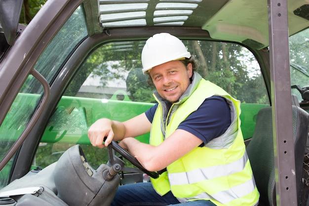 Un conductor de grúa sonriente en un sitio de construcción