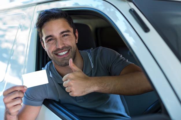 Conductor guapo mostrando los pulgares hacia arriba mientras sostiene la tarjeta en blanco