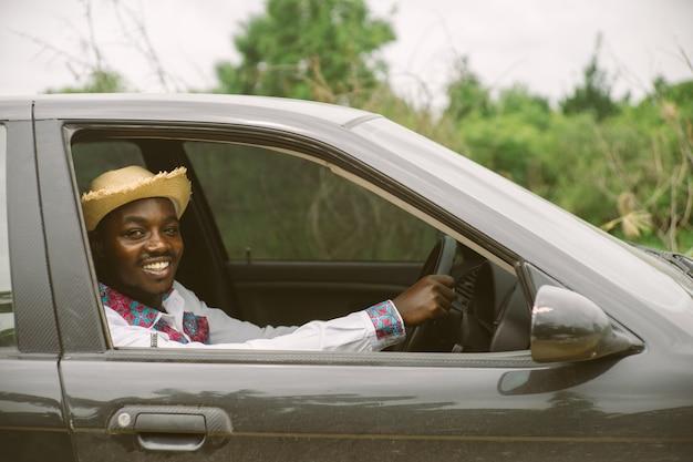 Conductor hombre africano sonriendo mientras está sentado en un automóvil con ventana delantera abierta