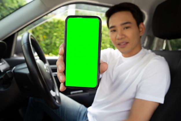 Conductor hombre asiático sentado en el coche y sosteniendo el teléfono móvil con fondo de pantalla verde