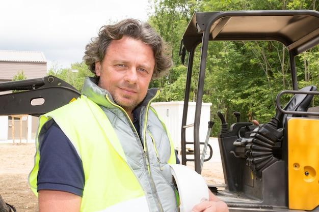 Conductor hombre constructor de pie delante de maquinaria de construcción en obra de construcción