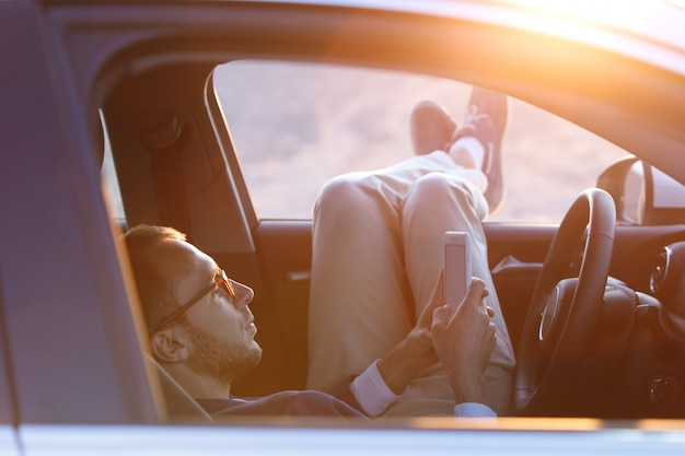 El conductor del hombre puso los pies en la puerta del automóvil, se relajó, disfrutó de una cálida tarde de verano, sintió el aire, se detuvo para descansar después de conducir, usando un teléfono inteligente.