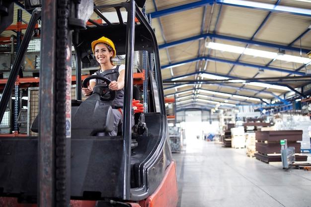 Conductor industrial femenino profesional operando la máquina de montacargas en el pasillo de la fábrica