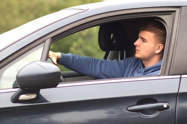 Conductor joven guapo está conduciendo un coche