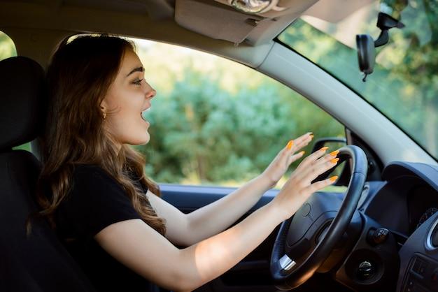 Conductor joven sentado en el coche con la boca abierta y llorando antes de accidente automovilístico.