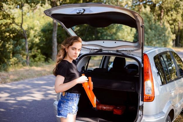 Conductor joven toma señal de emergencia desde el maletero del coche