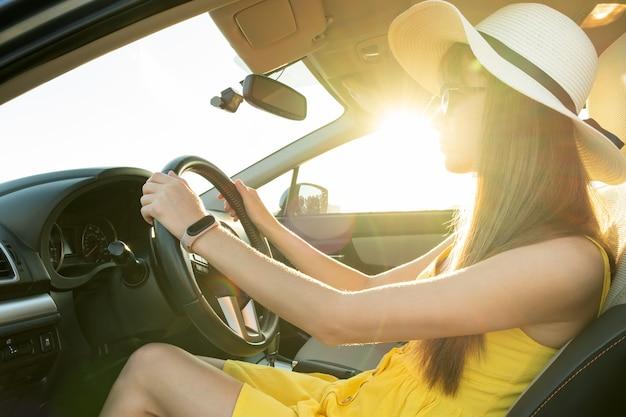 Conductor joven en vestido amarillo de verano y sombrero de paja conduciendo un coche