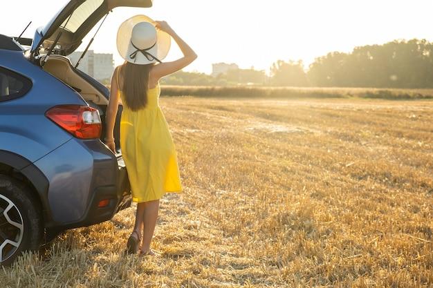 Conductor joven en vestido amarillo de verano y sombrero de paja de pie cerca de un coche disfrutando al atardecer.