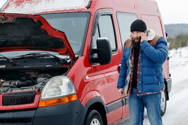 Conductor llame a asistencia técnica en la carretera en invierno