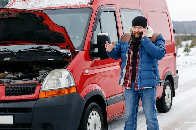 Conductor llame a asistencia técnica en la carretera en invierno.